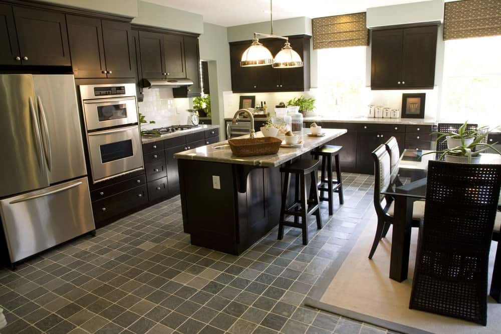 The brightness of the natural lights coming in from the windows are balanced by the dark brown tones of the wooden cabinets and drawers of the island and peninsulas. This is complemented by the different shades of gray tiles of the floor matching the stainless steel appliances.