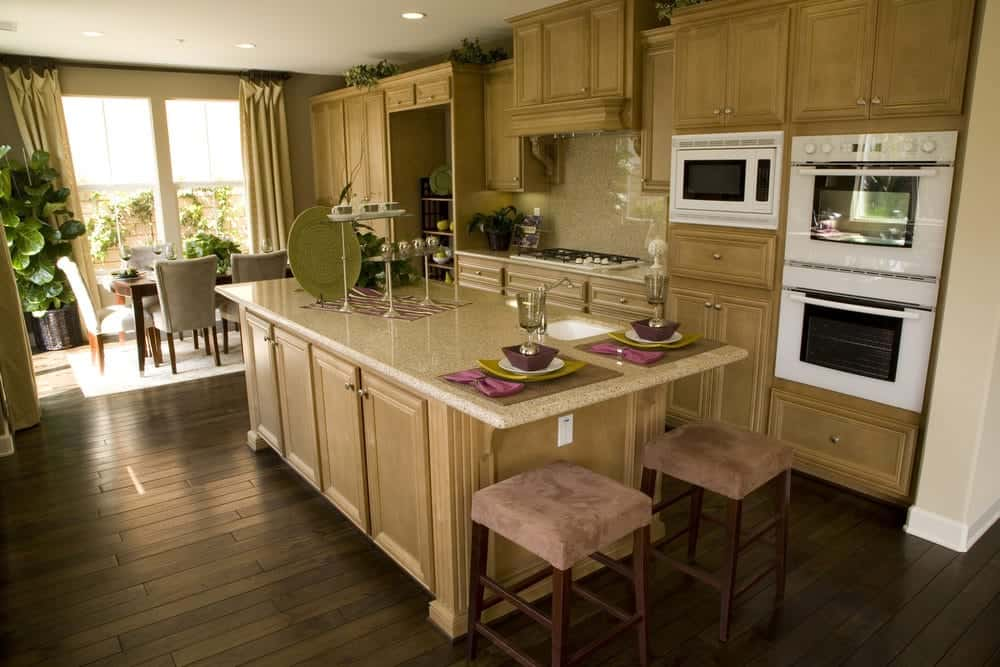 The dark hardwood flooring has a homey plank finish to it that complements the wooden cabinetry that has a slightly lighter shade. These are adorned with plants on the space between their top and the white ceiling that has recessed lights complementing the white modern appliances.