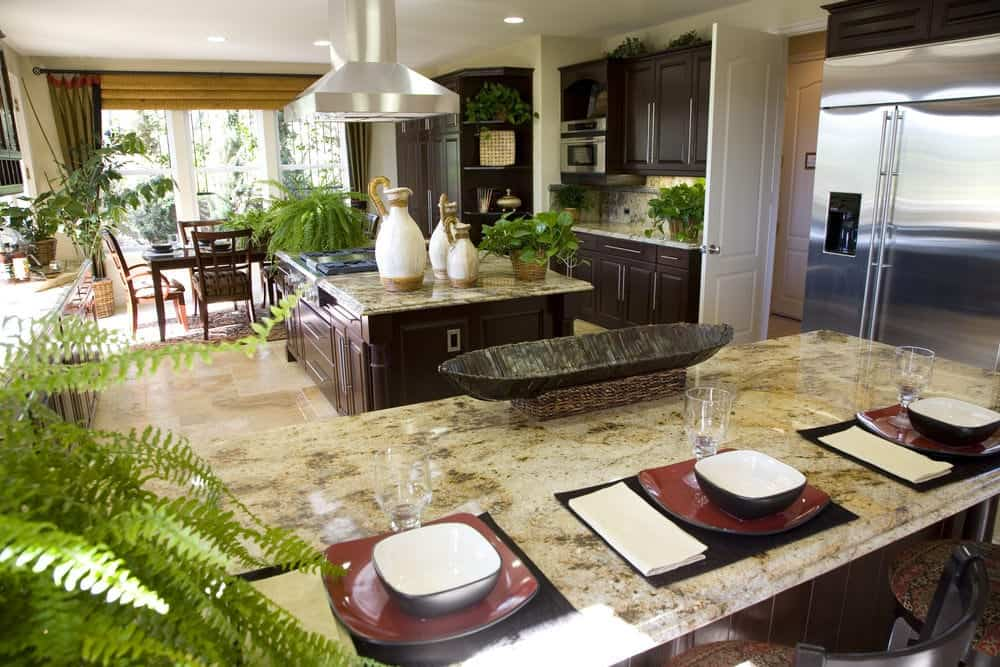 The various ferns and potted plants stand out in this Tropical-style kitchen that has dark brown cabinets and drawers paired with marble countertops that match the beige marble flooring tiles.