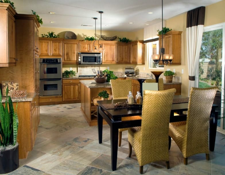 This kitchen shares its space with the dining area that has a black table and woven wicker chairs topped with a simple pendant light. This matches with the pendant lights hanging over the cooking area housed within the wooden cabinetry that is topped with various decors and potted plants.