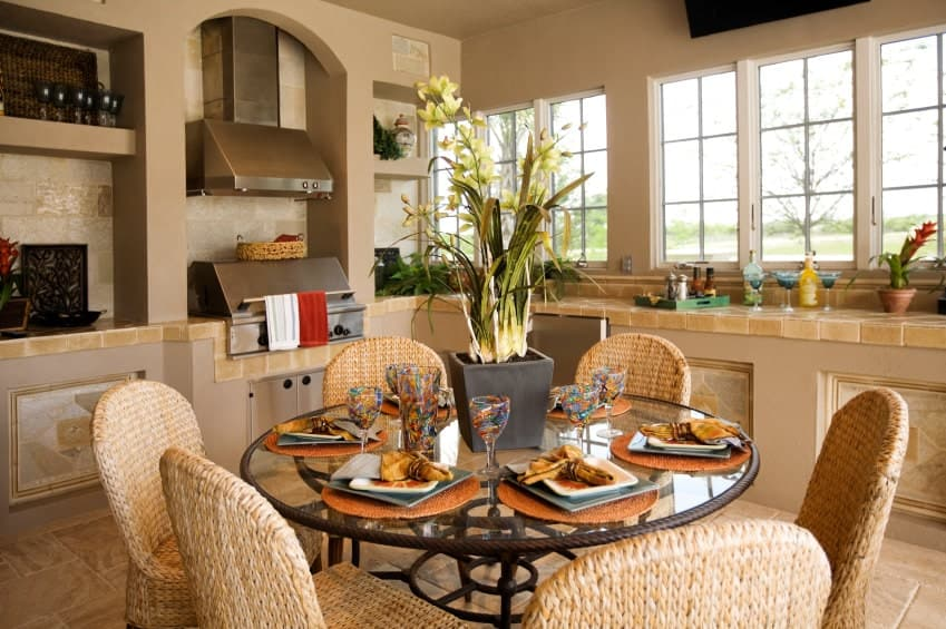 This charming and cozy kitchen has a small informal dining area right in the middle of its beige marble flooring. It has woven wicker chairs that match the tone of the countertop tiles as well as the decorative patterns on the L-shaped peninsula.