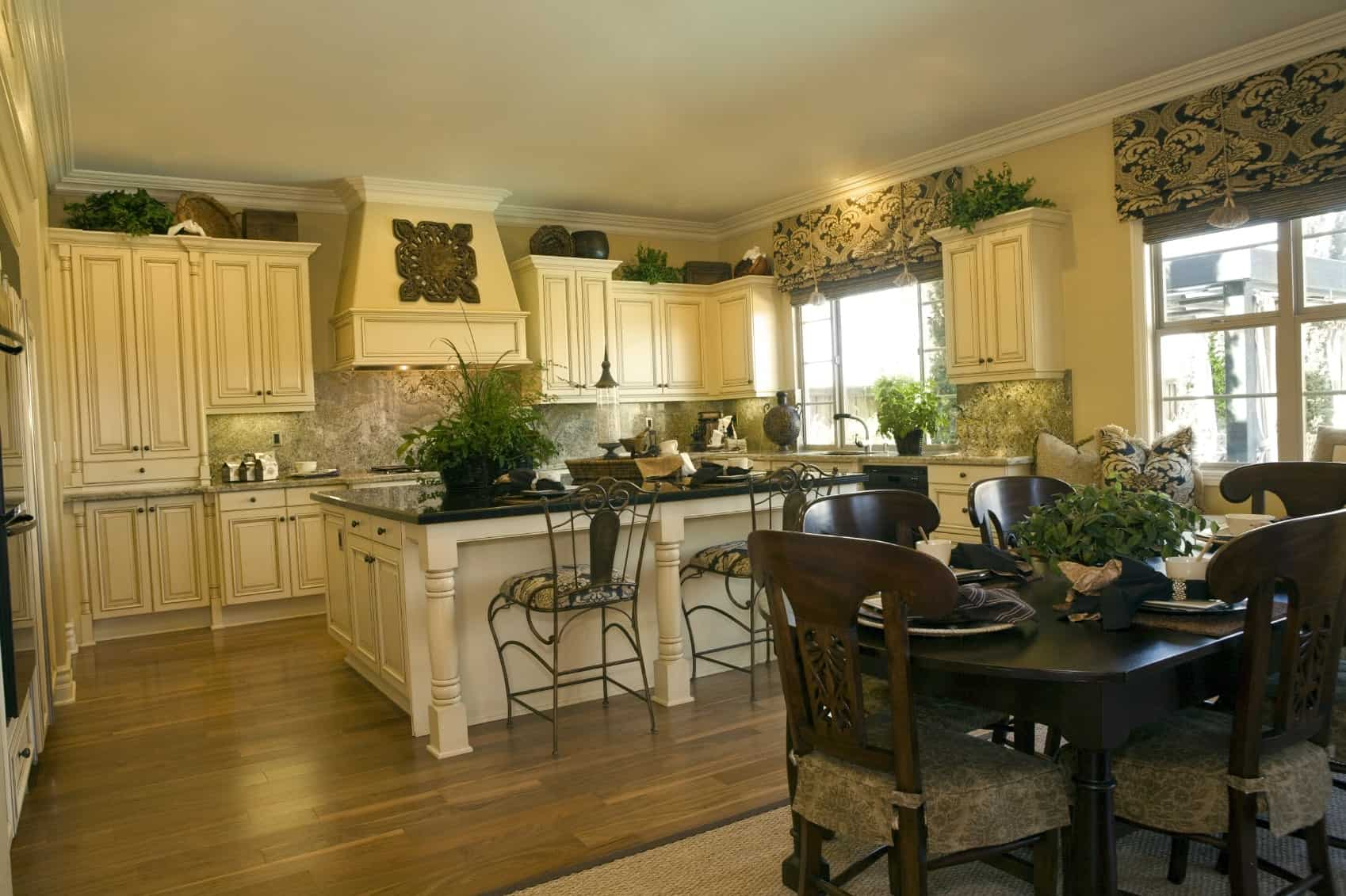 The beige vent hood of this Tropical-style kitchen is adorned with a large decorative artwork that somehow matches with the patterns of the window shades and the seat cushions of the wrought iron chairs paired with the kitchen island.