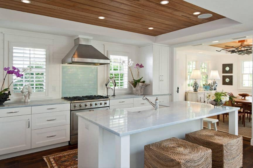 The stark white kitchen island shines bright together with the white shaker cabinets and drawers of the peninsula as well as the white walls that make the potted flowers stand out. This is balanced by the wooden middle tray of the ceiling and the hardwood flooring.