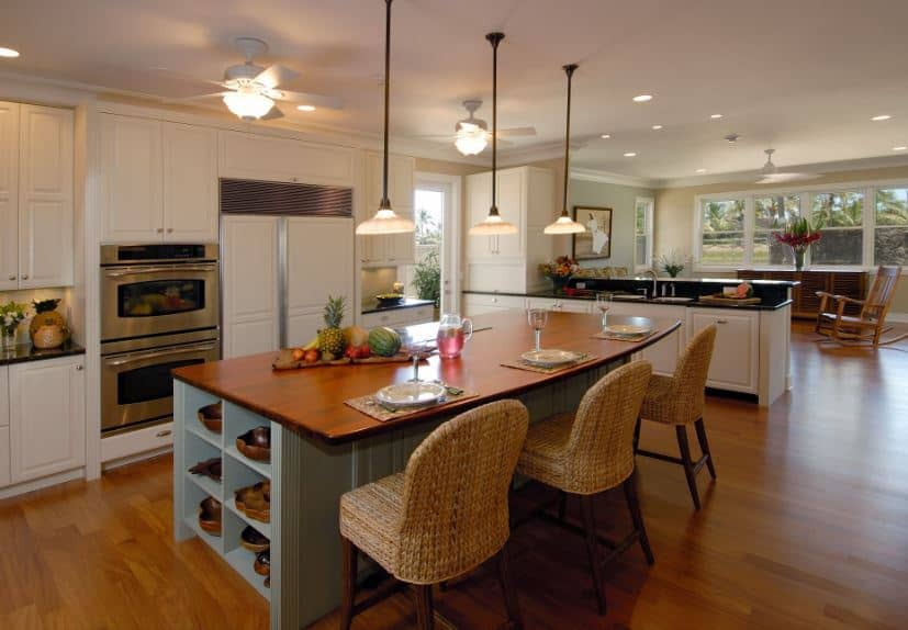 The woven wicker chairs complement the light blue wooden kitchen island as well as its wooden countertop with a built-in breakfast bar. These are all warmed by the various sources of warm yellow lights like the pendant lights and the ceiling fans.