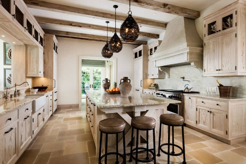 The charming decorative pendant lights stand out against the light wooden hues of the exposed wooden beams of the white ceiling. These beams match the wooden cabinetry of the two peninsulas and the large kitchen island in the middle.