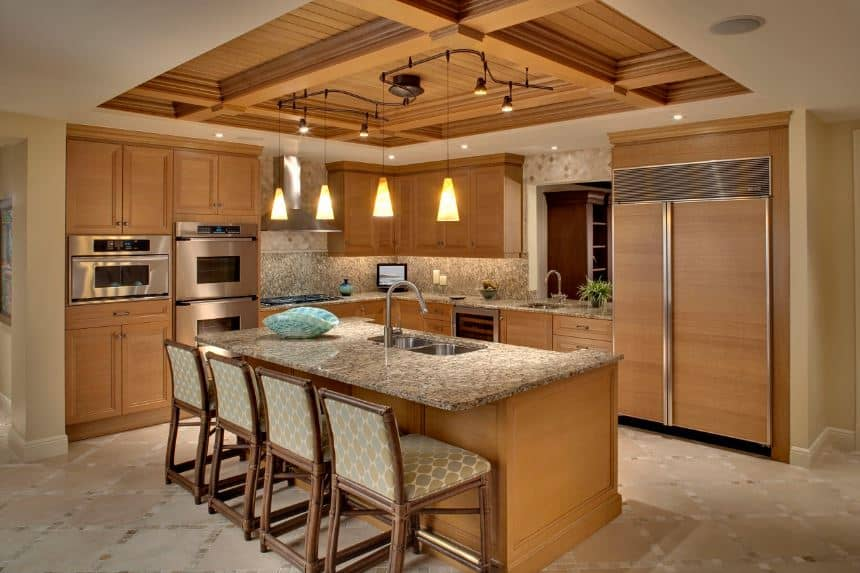 The elegant wooden coffered ceiling supports the four yellow pendant lights that casts a warm homey light on the wooden peninsula that also houses the stainless steel appliances. This is matched by the island that is paired with cushioned bamboo chairs.