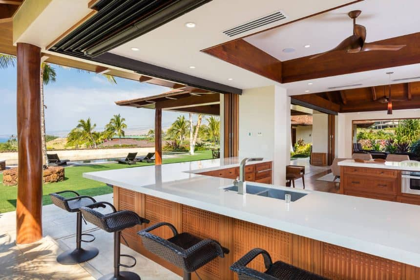 This is a beautiful kitchen that has a resort-style bar on the side with open walls that feature a charming tropical landscape filled with blue skies and tropical trees. This makes the white countertop shine against the wooden elements.