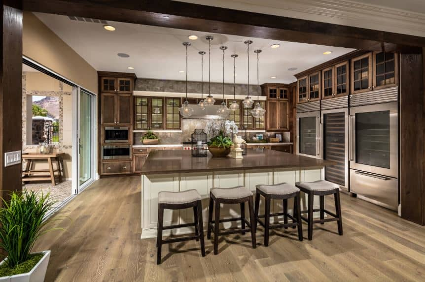 The hardwood flooring of this Tropical-style kitchen matches with the countertopof the large wooden kitchen island as well as the cabinetry of the kitchen peninsula on the far wall. Adjacent to this are the three large stainless steel appliances.