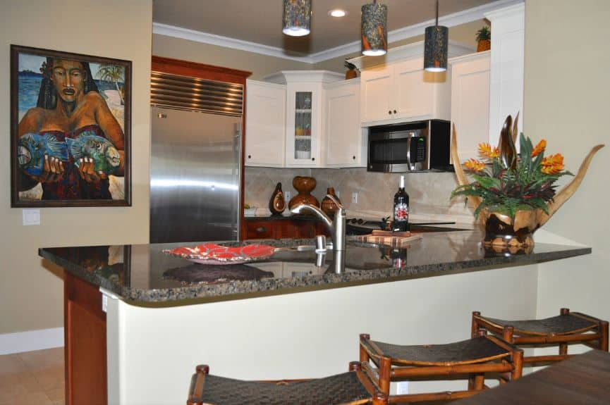 The emphasis of this Tropical-style kitchen would be the colorful painting of a woman holding a pair of fish mounted on the beige wall opposite the U-shaped wooden peninsula. This matches with the colorful hoods of the pendant lights hanging over the breakfast bar.