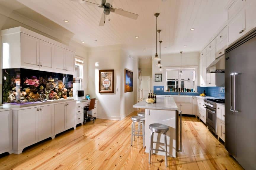 The highlight of this simple Tropical-style kitchen is the awesome aquarium that is housed by the white cabinet across from the small kitchen island with the same white cabinet that stands out against the hardwood flooring that is topped with a shilap white ceiling.