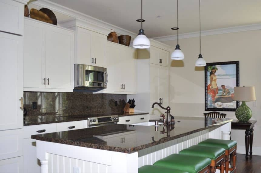 The colorful painting that is mounted on the far wall provides a nice dash of color for the simple white cabinetry of the kitchen island and peninsula contrasted by the dark gray countertops as well as the green leather cushioned seats of the stools.