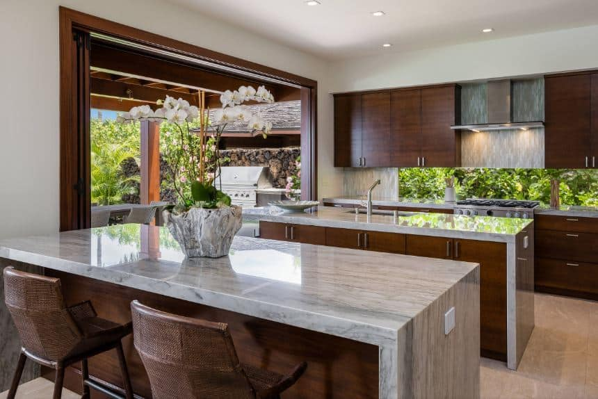 There is enough space for two white marble waterfall kitchen islands in this Tropical-style kitchen. This is matched by the rough white marble pot of the flower on the island serving as a breakfast bar that is paired with woven wicker stools.