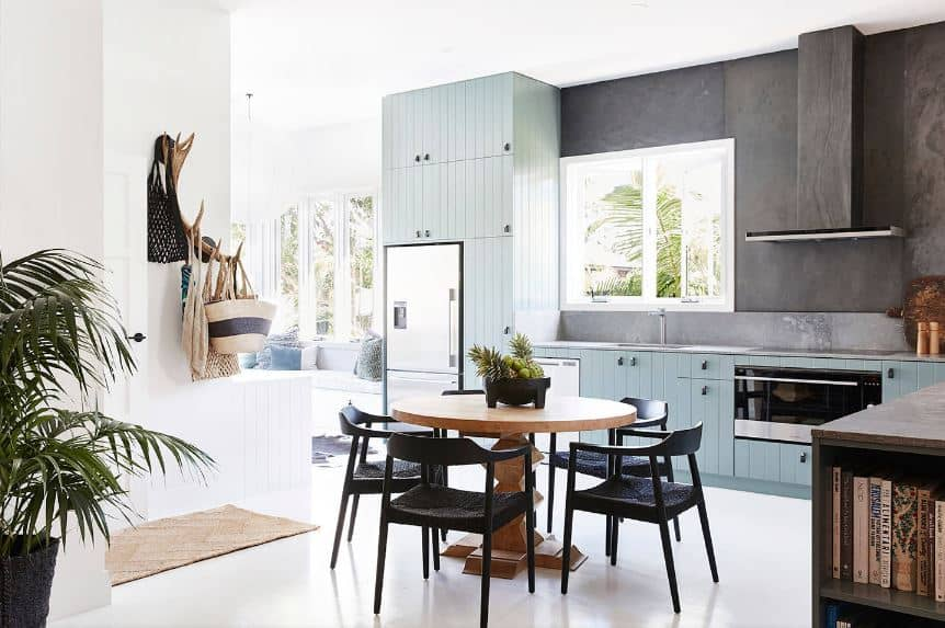 The light blue wooden structure of the kitchen peninsula of this Tropical-style kitchen has a plank finish and is augmented by the gray backsplash and the dark gray walls extending to the vent hood. This is contrasted by the bright white ceiling and flooring.
