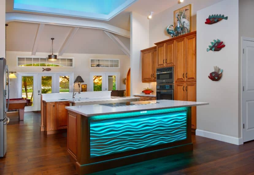 This Tropical-style kitchen has a beautiful wooden kitchen island that glows with blue light on one side that makes it seem like it is filled with swimming pool water. This is adorned with lovely fish artworks mounted on the beige wall beside the large wooden structure of the oven.