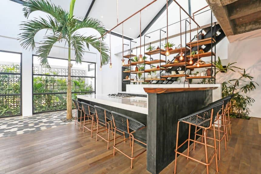 This awesome kitchen is a successful marriage of the Tropical-style and the Industrial-style. The hardwood flooring works well with the brass legs of the chairs and stools that are partnered with wooden kitchen island that is adorned on one end by a tall tropical tree planted right on the floor.