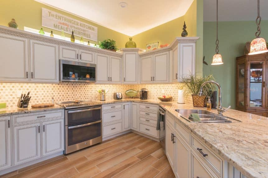 This Tropical-style kitchen has only enough space for a U-shaped peninsula that has light gray shaker cabinets and drawers that are complemented by the hardwood flooring and the polka-dot patterned backsplash that are lit with warm yellow lights.