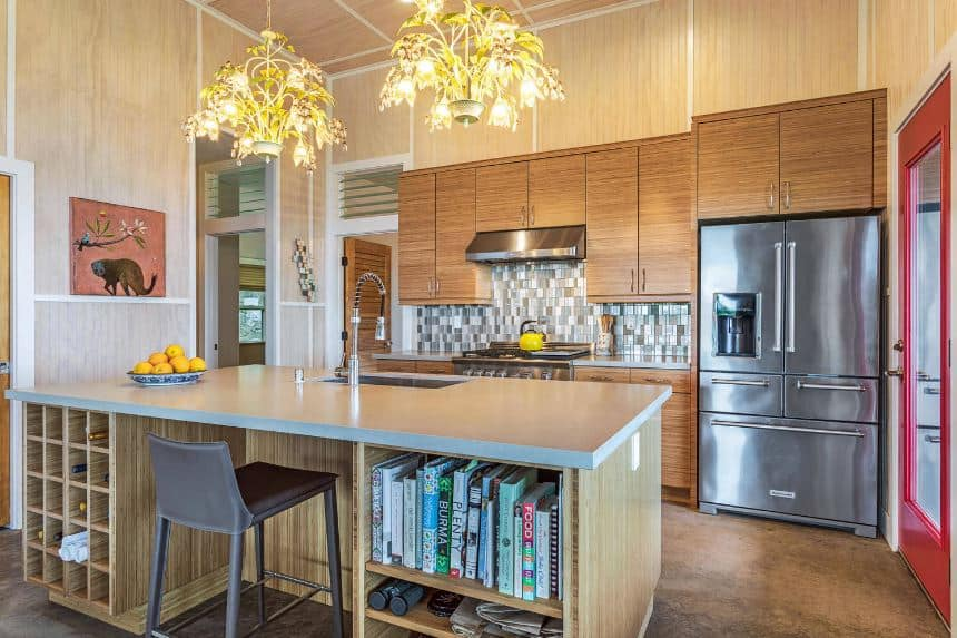 The beautiful decorative chandeliers hanging over the wooden kitchen island have flower-like design to it. This serves as a highlight to the simple wooden tones of the walls, cabinetry and flooring that are all contrasted by the stainless steel appliances and the blue tiles of the backsplash.