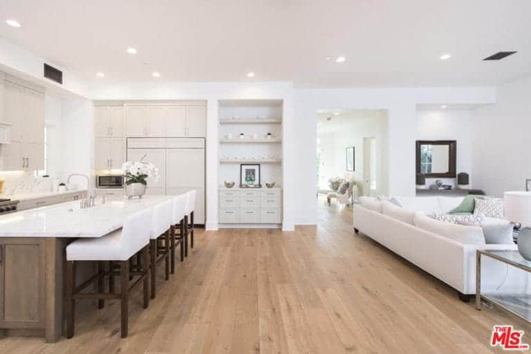 The white modern wooden stools pairs well with the white countertop of the wooden kitchen island that complements the light hardwood flooring that is brightened by the white ceiling and its recessed lights.