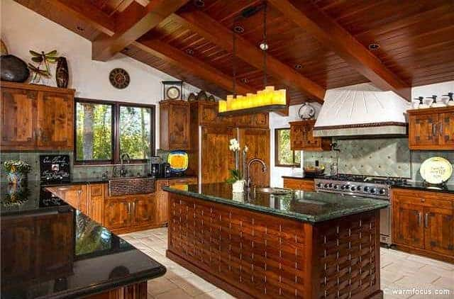 The wooden shed ceiling has exposed wooden beams that contrast the white upper walls. These white upper walls are adorned with various decors and dishware placed on the tops of the wooden floating cabinets with the same hue as the peninsula and its kitchen island.