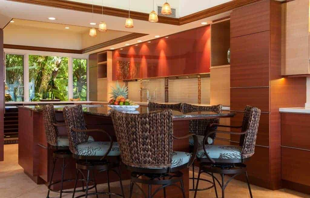 The wide glass window at the far end of the L-shaped kitchen peninsula provides a nice green contrast for the redwood cabinetry. The island has a table attached to it that serves as the breakfast bar for the woven wicker chairs with patterned seat cushions.