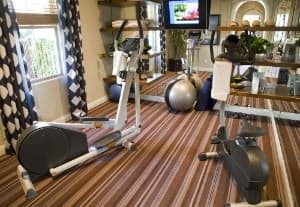 Home gym with carpet, exercise ball and elliptical machine.