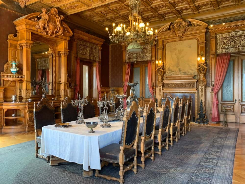 Formal dining room with a long dining table and black leather chairs that sit on a gray bordered rug. It includes a carved wood cabinet with an arched mirror and a vintage chandelier that hung from the ornate ceiling.
