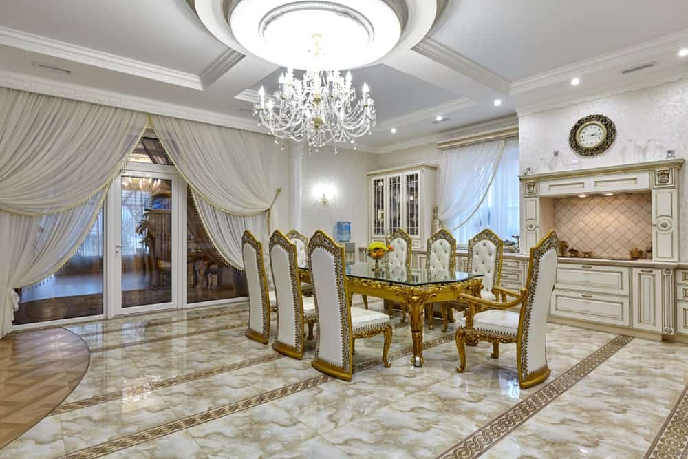 Expansive dining area boasts a crystal chandelier and an elegant dining set on a marble tile flooring. It is placed across the white cabinetry and stove alcove accented with a round wall clock.