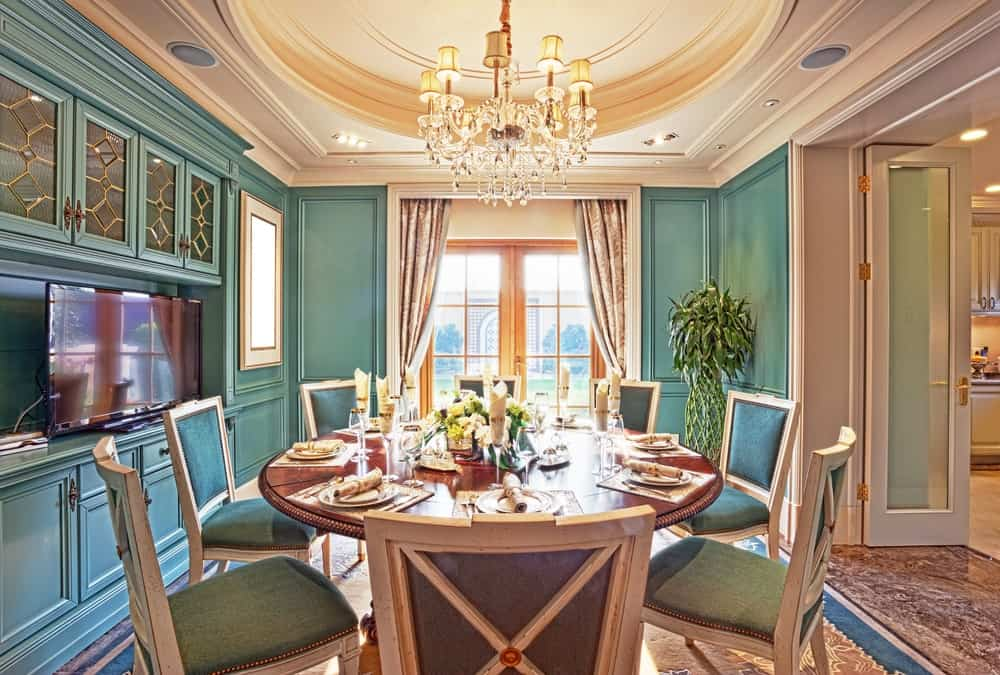 Victorian dining room offers a round dining table and blue upholstered chairs that complement the wainscoted walls and cabinetry. It includes a crystal chandelier and a French door leading out to the lush green yard.