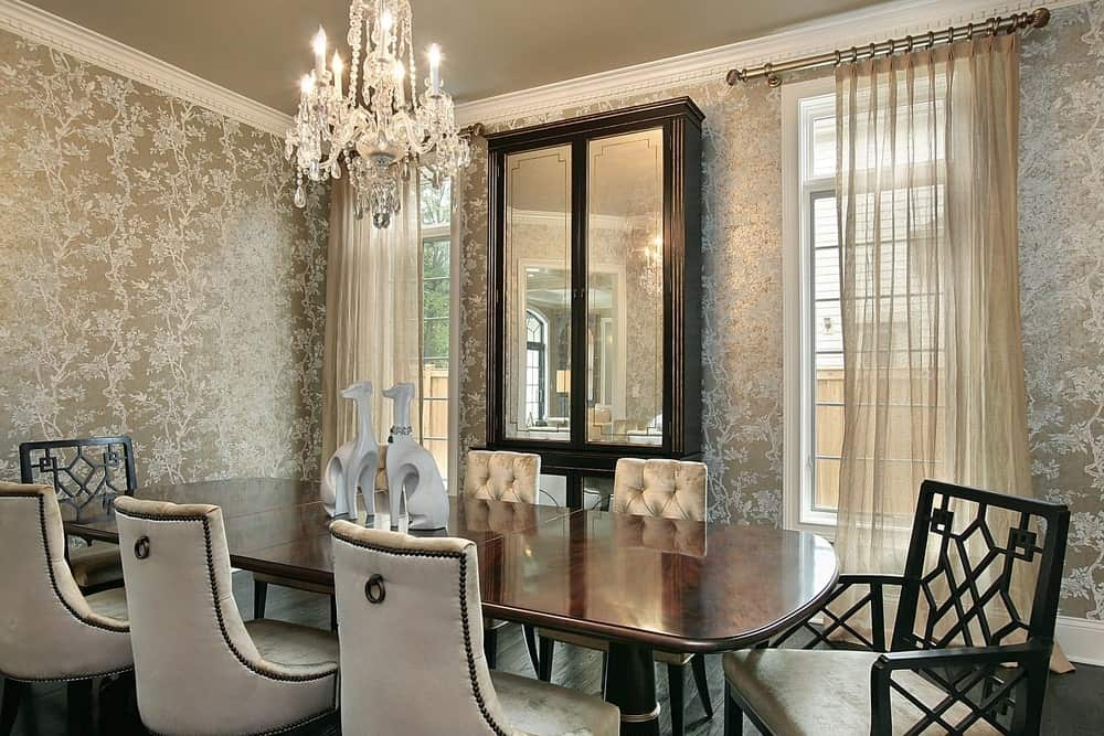 Classy dining room by the white framed windows covered in sheer curtains. It has a mirrored cabinet and beige cushioned chairs surrounding a wooden dining table lighted by a fabulous chandelier.