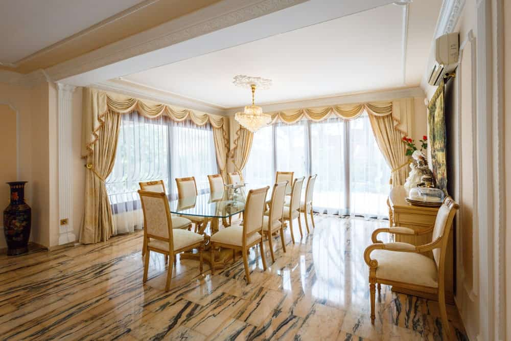 Spacious dining room with tiled flooring and full height glazing dressed in elegant drapes and valances. It includes a crystal chandelier and glass top dining table paired with yellow upholstered chairs.