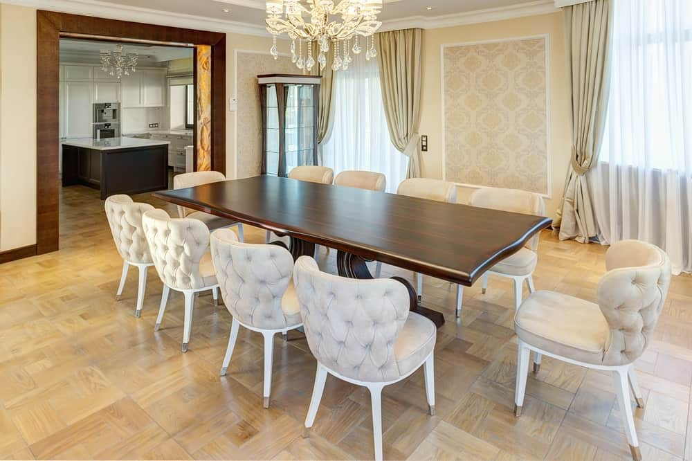 This dining room boasts a smooth, dark wood dining table and tufted wingback chairs on tiled flooring. It has a gorgeous chandelier and display cabinet adjacent to the glazed window covered with beige drapes and white sheer curtains.