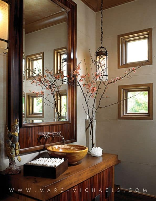 Asian powder room showcases a wooden vessel sink vanity with a matching mirror illuminated by a pendant light.