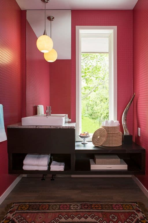 Charming powder room with pink walls and hardwood flooring topped by a shabby chic rug. It has a wooden floating sink vanity and a frameless mirror beside the glass window.