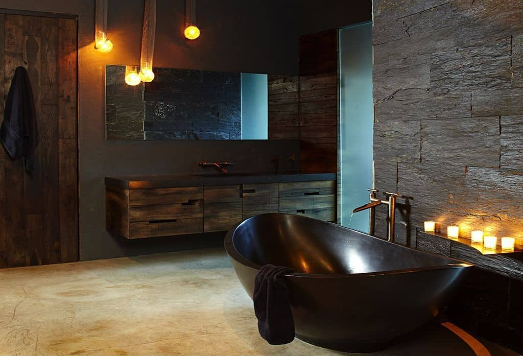 Spacious primary bathroom with black walls matching the black freestanding tub. There's also a rustic floating vanity matching the rustic bathroom door.