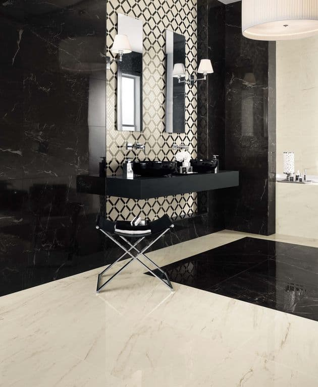 A primary bathroom with elegant black and white marble tiles walls and floors, along with a stylish black floating vanity with two black vessel sinks.