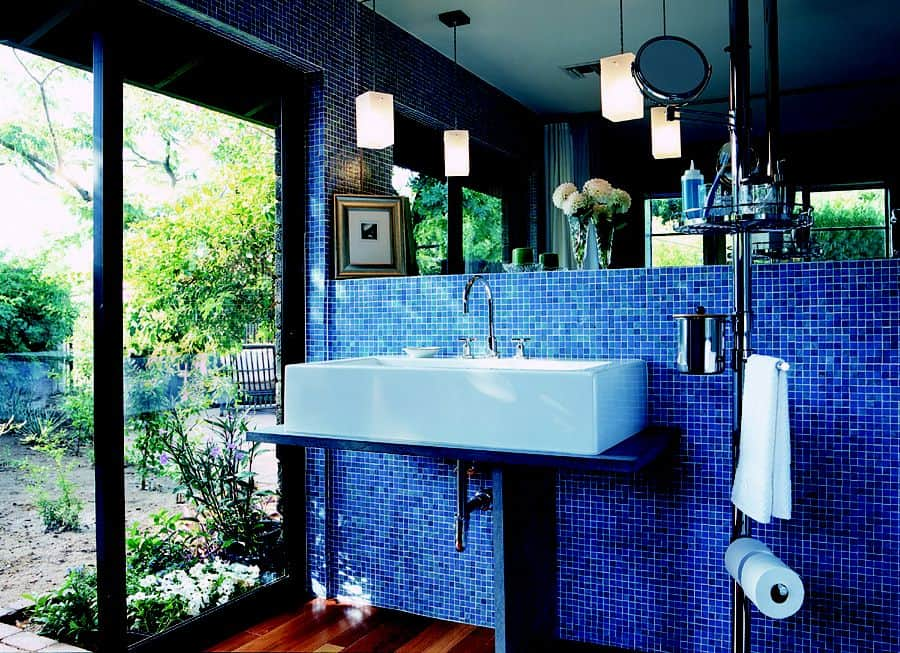 Natural light from the glass windows and door illuminates this bathroom along with pendant lights that hung over the washstand that's fixed to the mosaic tiled wall.