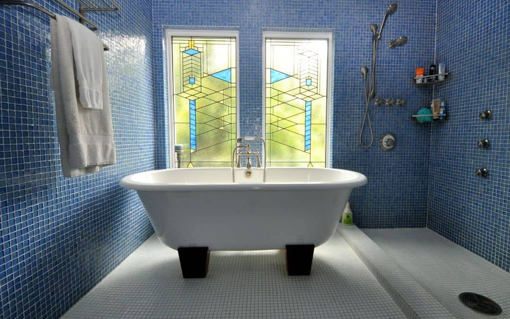 A modish primary bathroom boasting a combination of blue and white tiles walls and floors. There's a large freestanding tub an open shower on the corner.