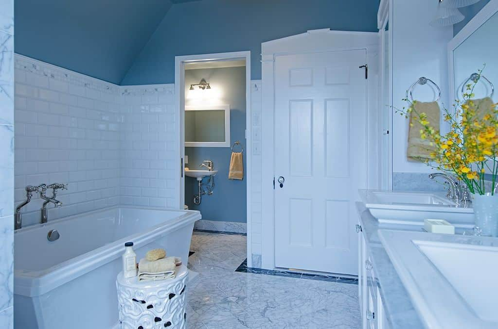 This master bathroom boasts classy tiles flooring and blue walls. The room features a freestanding tub and two sinks, along with a toilet area.