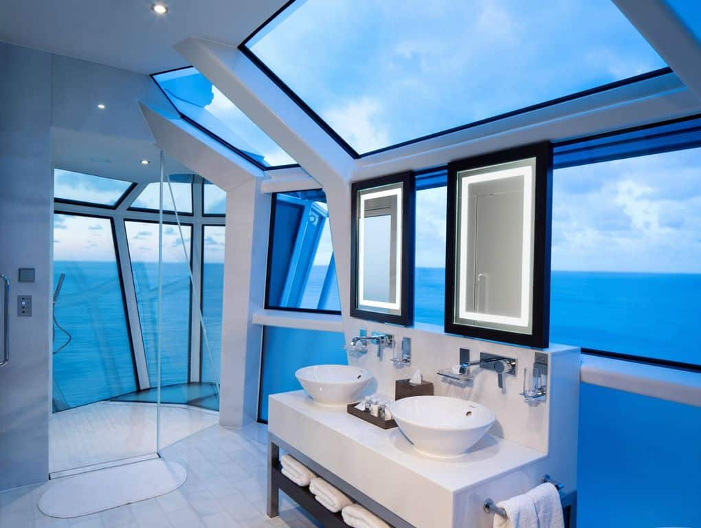 Contemporary primary bathroom with blue walls and multiple glass windows overlooking the jaw-dropping ocean view.