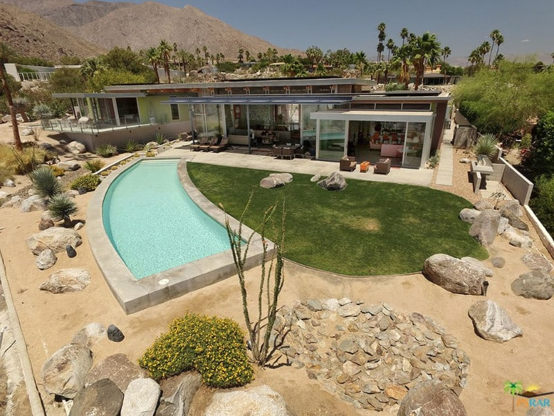 This modern bungalow-style home features a custom pool and a classy patio area.