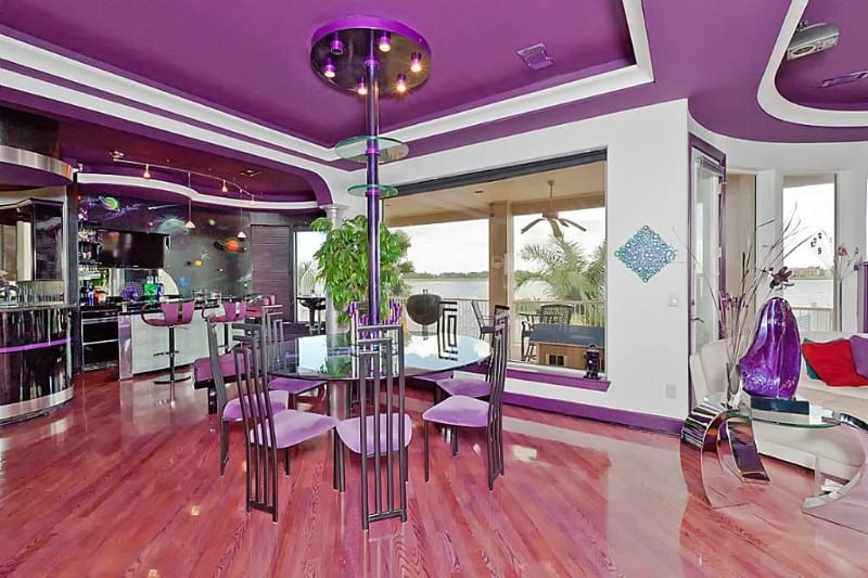 Purple wall dining room with hardwood floors and round table.