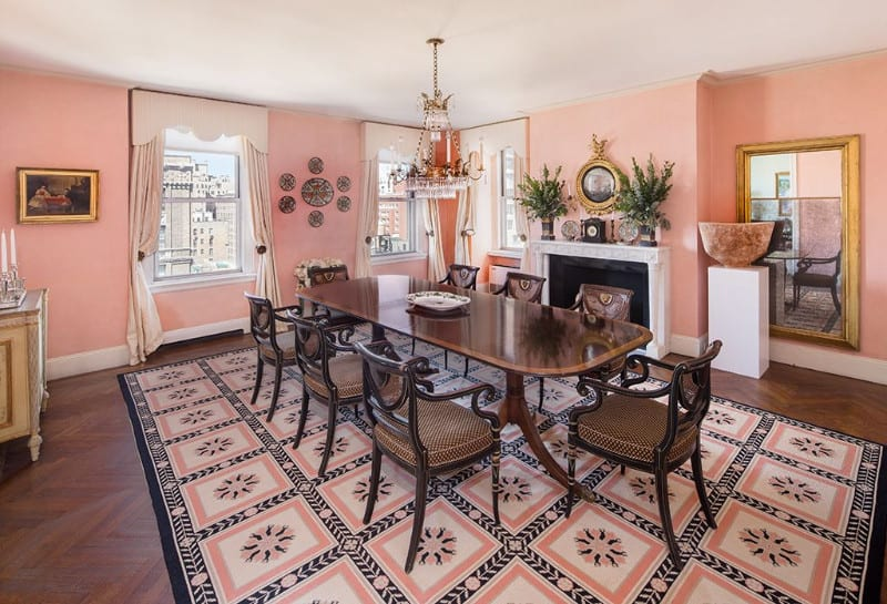 Charming dining room with pink walls and herringbone flooring topped by a lovely patterned rug. It includes a glossy darkwood dining table surrounded with cushioned chairs.