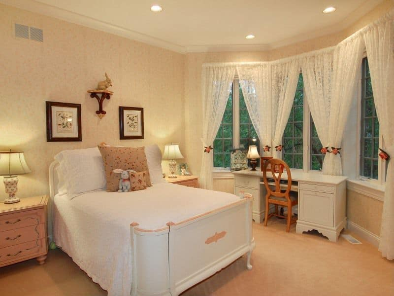 Small girl's bedroom with white classy walls and window curtains. The desk is placed near the windows overlooking the beautiful outdoor area surrounding the house.