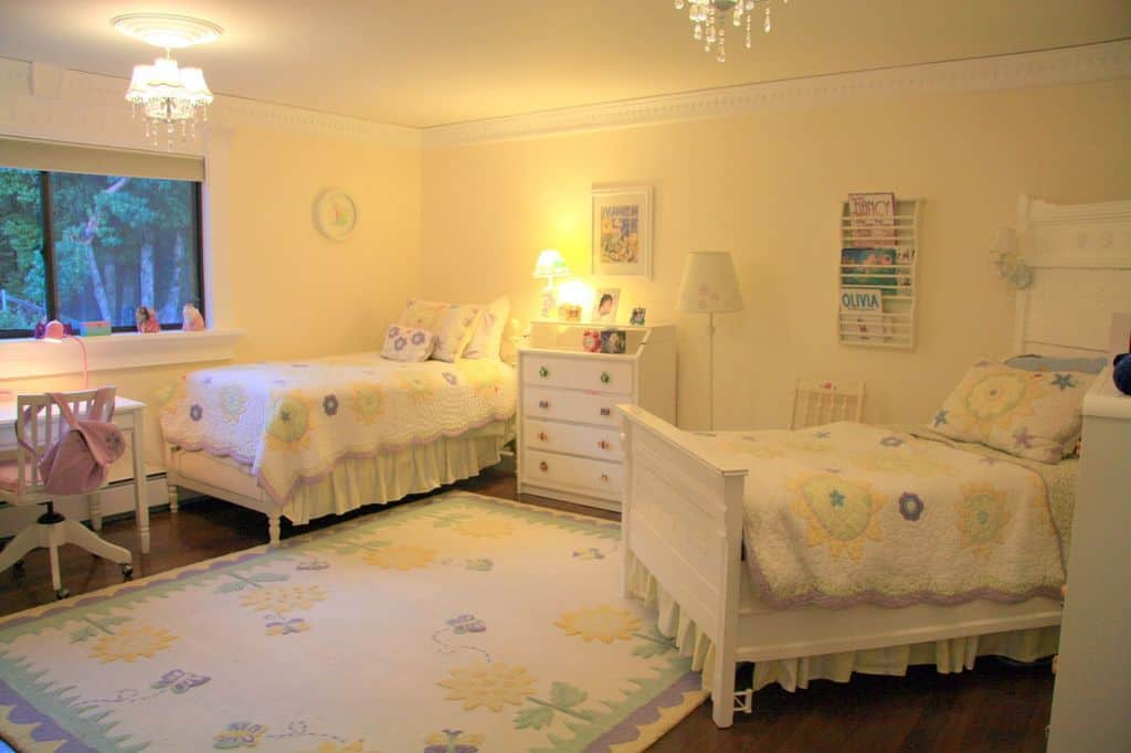 This girls bedroom offers two beds and a cute rug set on the hardwood flooring. The warm white lights look perfect together with the white walls.