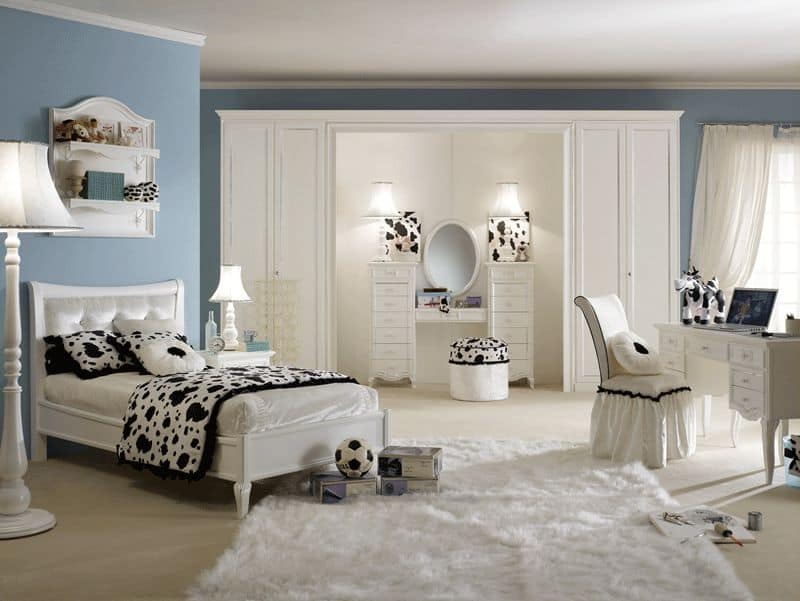 Large girl's bedroom with black and white accent all over the space. The carpet flooring looks classy. There's a powder space and a study area in the room.