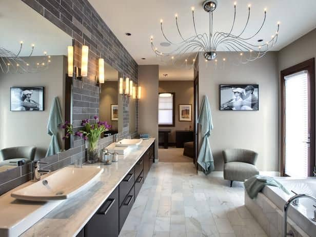 Large primary bathroom with a glamorous ceiling light and romantic wall lights. The two sinks look beautiful as well as the bathtub.