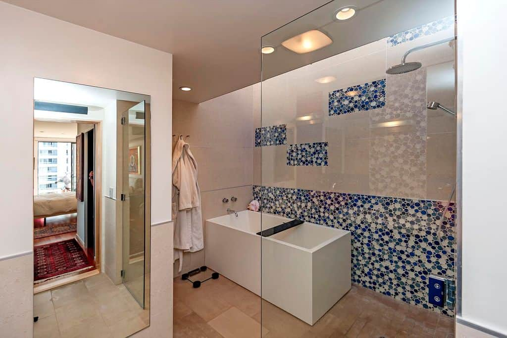 This primary bathroom boasts very attractive blue and white walls near the freestanding tub and an open shower room.