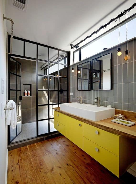 Industrial bathroom accented with a yellow floating vanity that's topped with a wooden counter and a vessel sink. It has a walk-in shower enclosed in a metal framed glass.