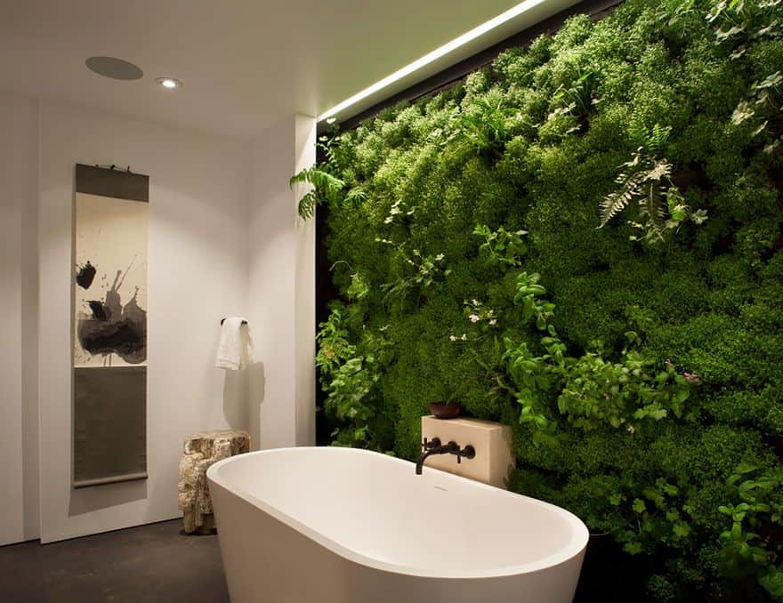 This charming bathroom offers a freestanding tub surrounded by a wall of lovely greens.
