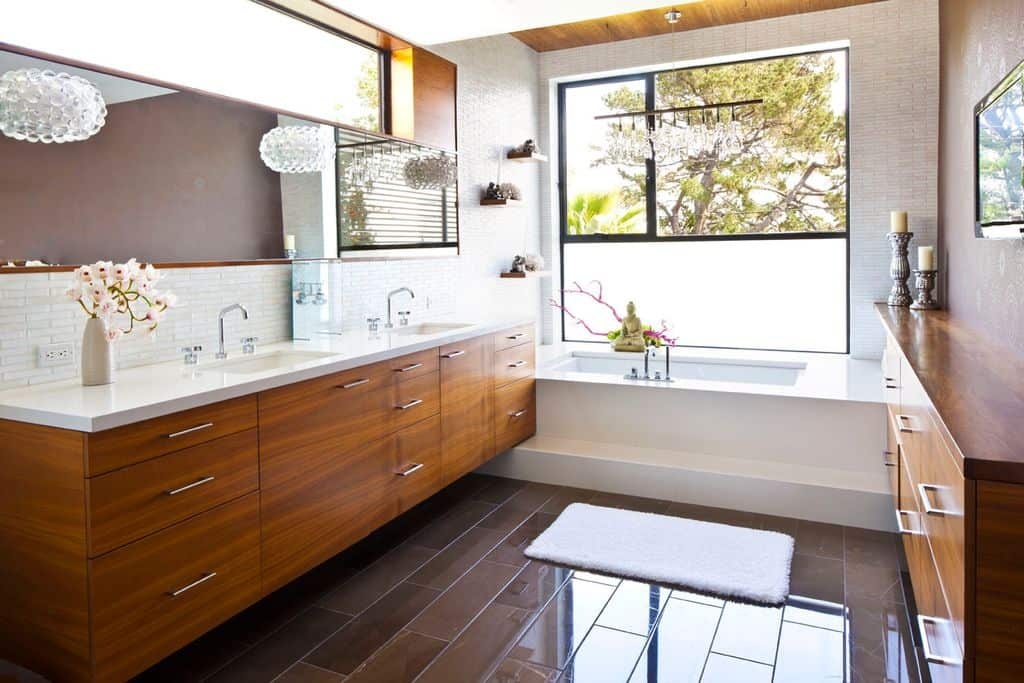 This beautiful modish primary bathroom offers sparkling tiles flooring and walls. The bathtub looks so gorgeous set near the window. The bathroom counter with two sinks looks very classy as well.